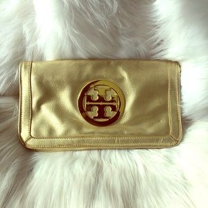 Gold Tory Burch clutch bag with shoulder strap